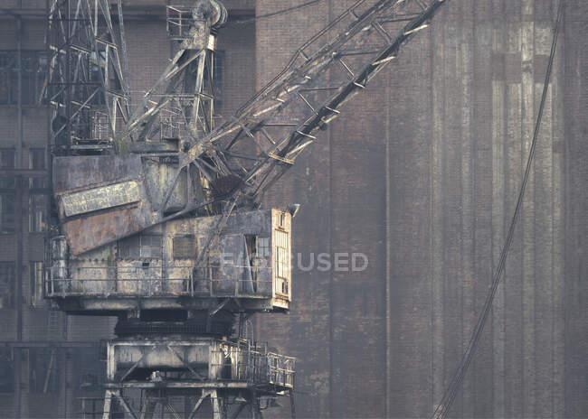Старий іржавий журавель перед покинутим будинком на фабриці (Великобританія). — стокове фото