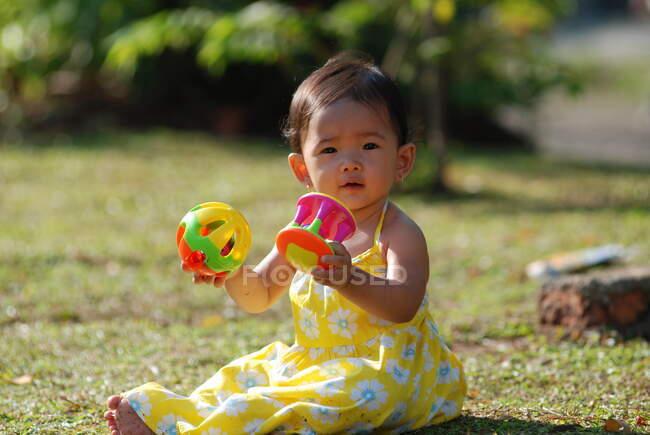 Дівчинка сидить у парку, граючи з іграшками, Індонезія. — стокове фото