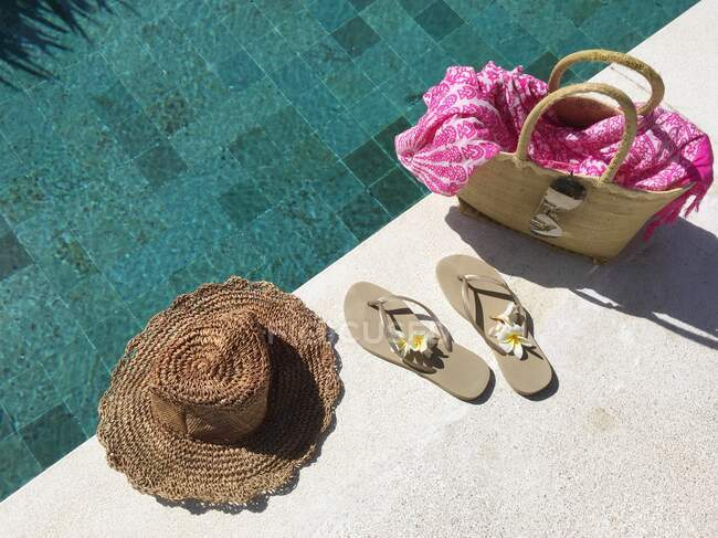 Flip-flops and a basket with summer accessories by a swimming pool — Stock Photo