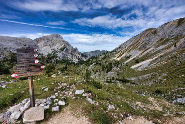 Cuatro excursionistas más allá de una señal de senderismo, Dolomitas, Parque Natural Fanes-Sennes-Braies, Tirol del Sur, Italia - foto de stock