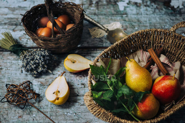 Pears, eggs and cinnamon sticks on a wooden table — Stock Photo