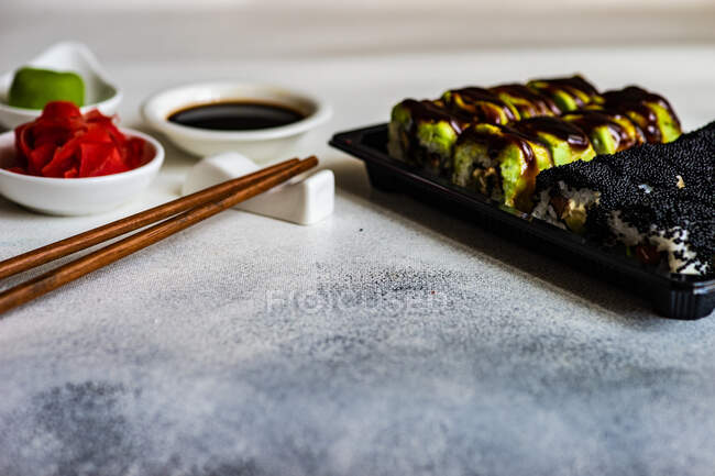 Sushi maki rolls with pickled ginger, wasabi, soy sauce and chopsticks — Stock Photo
