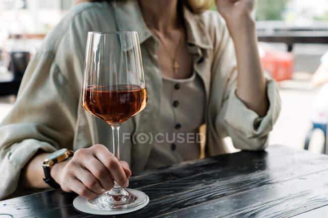 Жінка сидить за столом і насолоджується келихом рожевого вина. — стокове фото