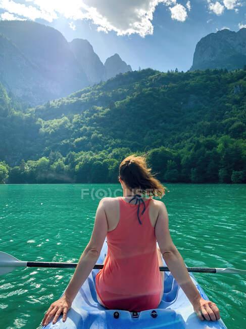 Rear view of a young woman kayaking, Molveno lake, Trentino, Italy — Stock Photo