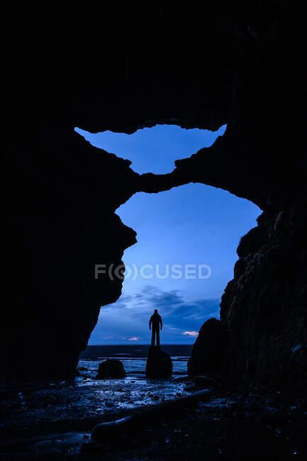Vista desde una cueva de un hombre de pie sobre una roca en el mar, Islandia - foto de stock