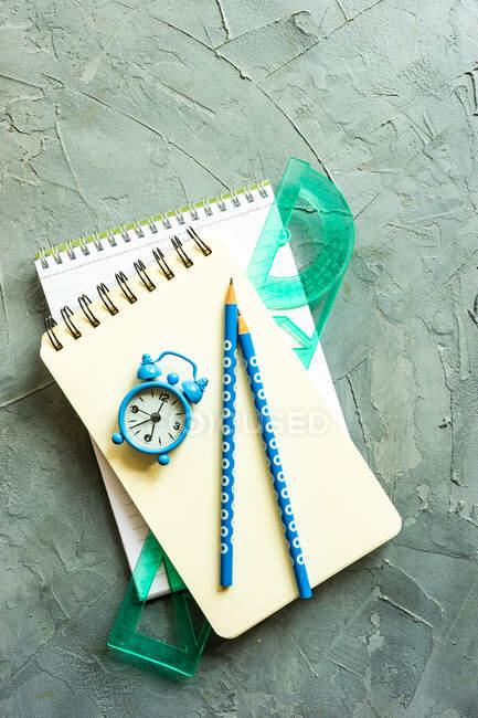 Блокноти, олівці, лінійка і будильник. — стокове фото