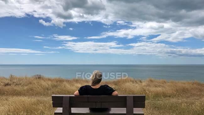 Rückansicht einer Frau, die auf einer Bank sitzt und die Aussicht betrachtet, Barton on Sea, Hampshire, England, UK — Stockfoto