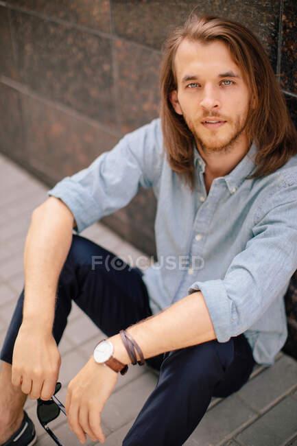Retrato de un hombre guapo sentado en el suelo apoyado contra una pared, Rusia - foto de stock