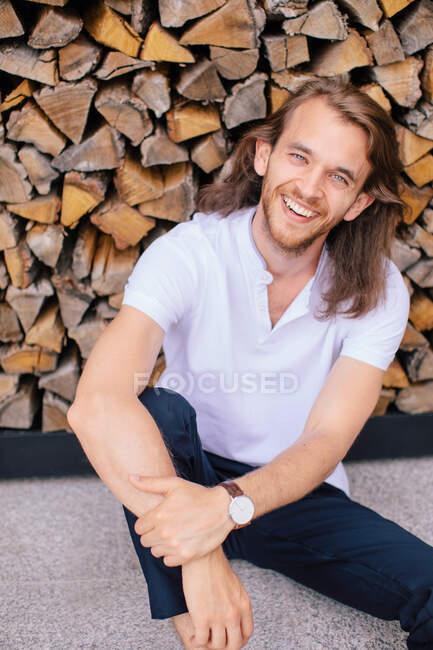 Retrato de un hombre guapo sentado en el suelo apoyado sobre una pila de troncos, Rusia - foto de stock