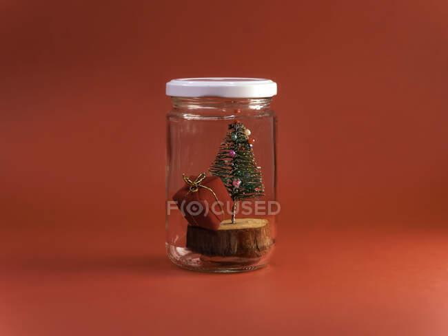 Árbol de Navidad y regalo en un frasco de vidrio - foto de stock