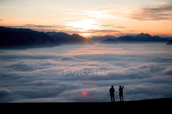 Silueta de dos mujeres en un pico de montaña al atardecer mirando a la vista, Salzburgo, Austria - foto de stock
