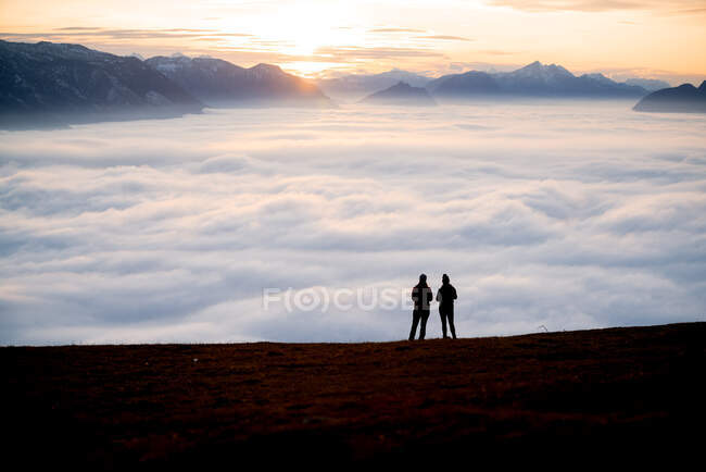 Silhouette of two women on a mountain peak at sunset looking at the view, Salzburg, Austria — Stock Photo