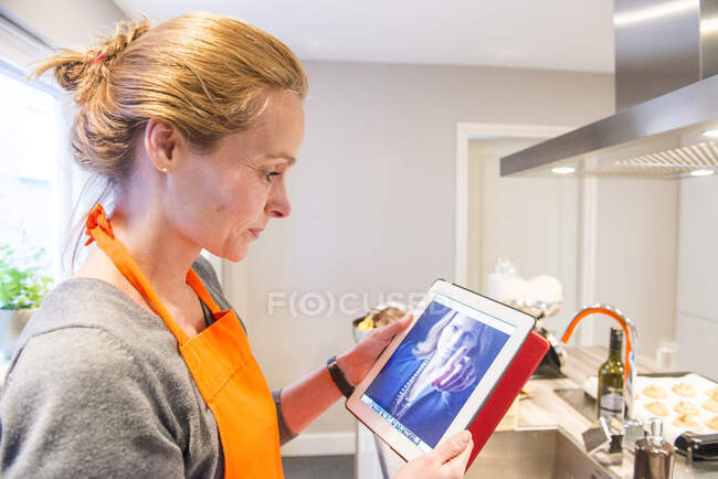 Donna in piedi in cucina guardando una foto sul suo tablet digitale — Foto stock