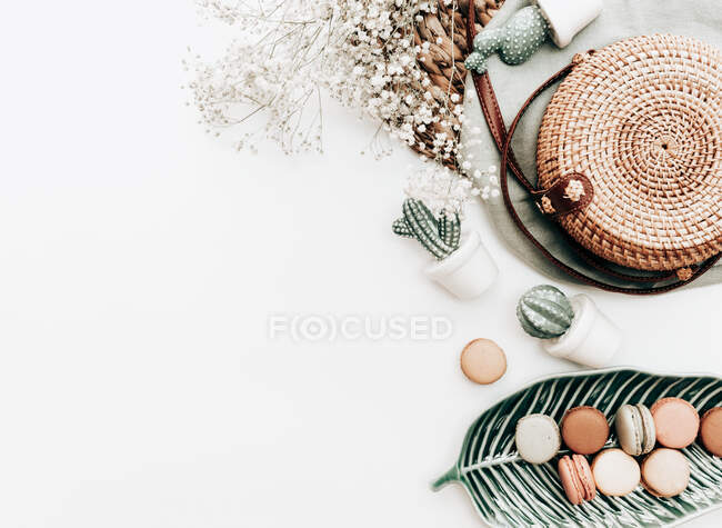 Macaroons on a leaf shaped dish, flowers, cactus decorations and a basket on a white background — Stock Photo