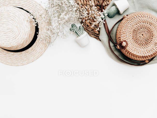 Macarrones sobre un plato en forma de hoja, flores, decoraciones de cactus y una cesta sobre un fondo blanco - foto de stock