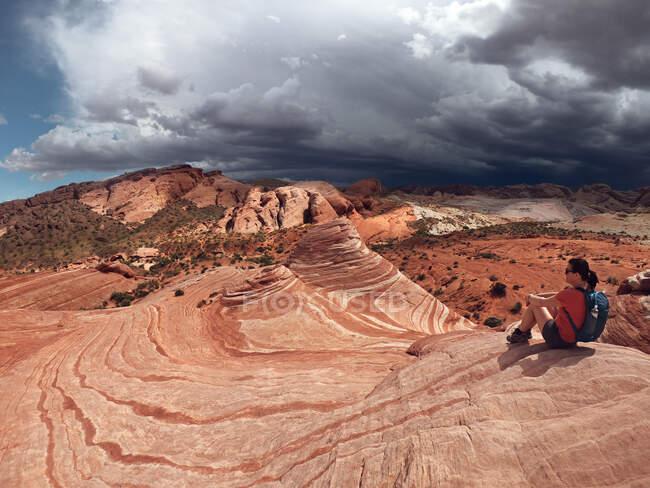 Mujer sentada en las rocas, Valley of Fire State Park, Nevada, EE.UU. - foto de stock