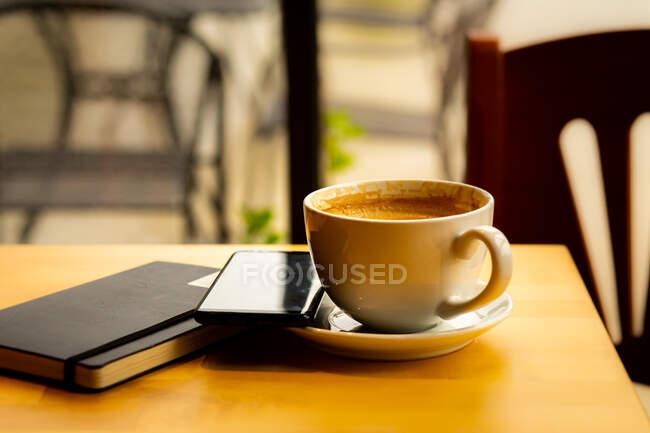 Taza de café, portátil y teléfono móvil en una mesa en una cafetería - foto de stock