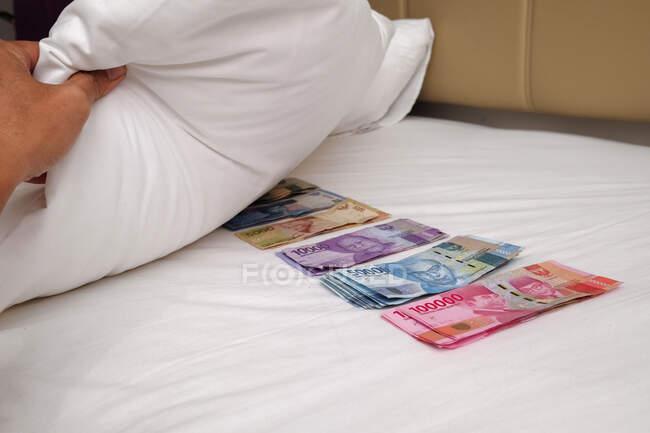 Homem escondendo notas indonésias debaixo de uma almofada — Fotografia de Stock