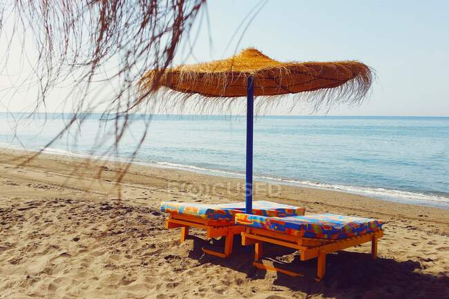 Dos tumbonas bajo una sombrilla en la playa, Málaga, España - foto de stock