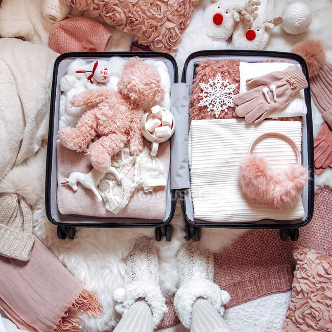 Woman standing next to an Open suitcase filled with clothing, travel accessories and a teddy bear — Stock Photo