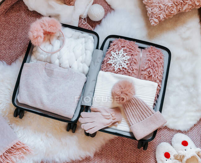 Open suitcase filled with clothing, travel accessories and a teddy bear — Stock Photo