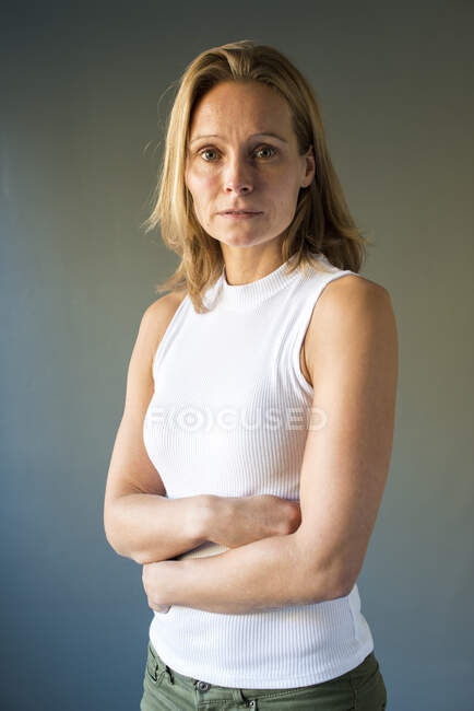 Portrait of a blonde woman with her arms crossed — Stock Photo