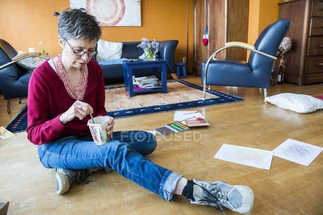 Портрет зрілої жінки, що сидить на підлозі з гарячим напоєм. — стокове фото