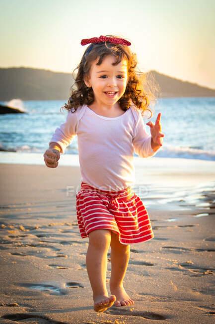 Souriante fille courant sur la plage avec une poignée de sable, Brésil — Photo de stock