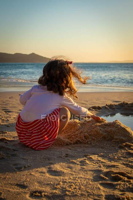 Ragazza sulla spiaggia giocando con la sabbia, Brasile — Foto stock