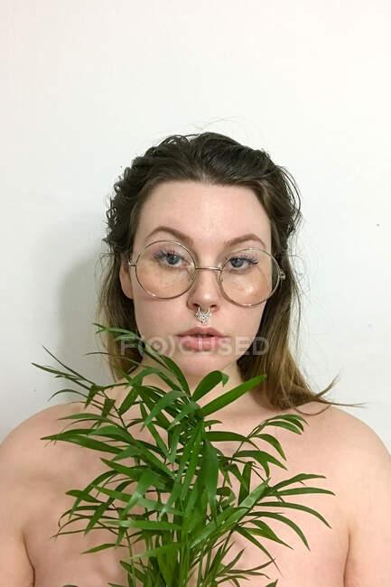 Retrato de uma mulher usando óculos segurando uma palmeira de salão — Fotografia de Stock