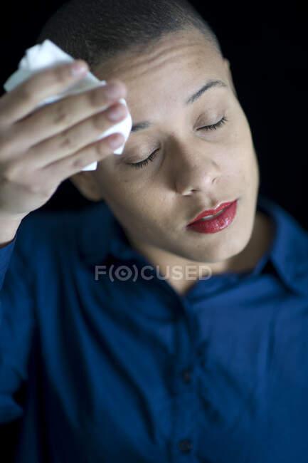 Портрет женщины с короткими волосами, вытирающей лоб — стоковое фото