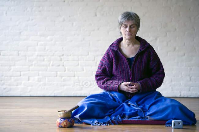Портрет пожилой женщины, сидящей со скрещенными ногами — стоковое фото