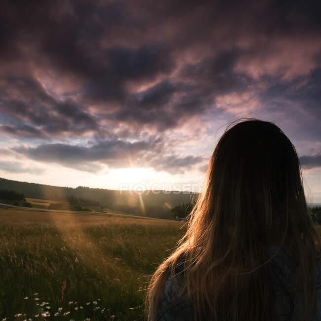 Rückansicht eines jugendlichen Mädchens, das bei Sonnenuntergang auf einem Feld steht, Frankreich — Stockfoto