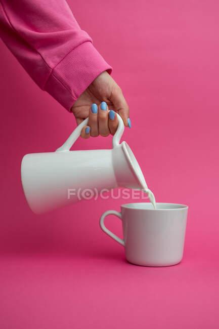 Простягла руку, тримаючи керамічний глек і полила молоко на чашці на рожевому фоні. — стокове фото