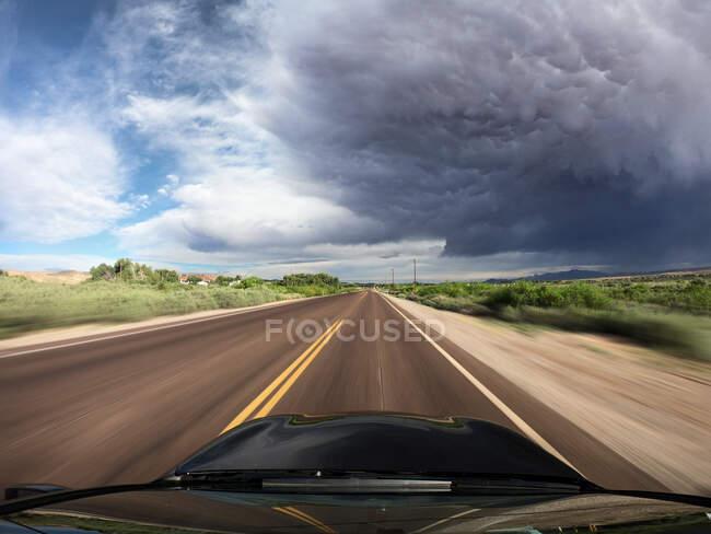 Автомобиль едет по дороге с приближающимся штормом, долина Моапа, Невада, США — стоковое фото