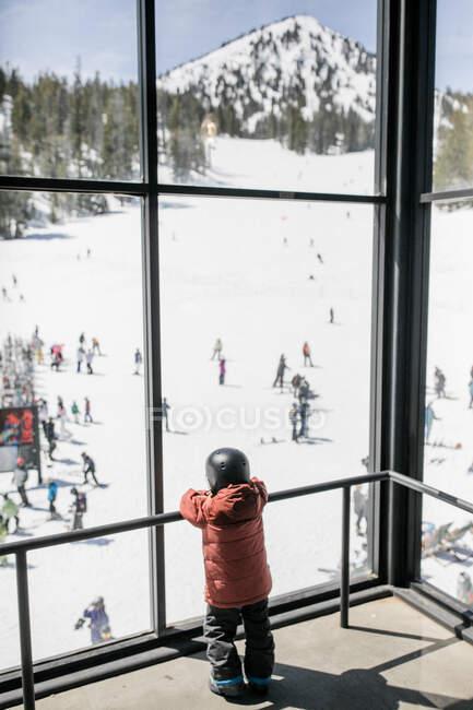 Мальчик в лыжной одежде, смотрящий в окно, Мамонт Лейкс, Калифорния, США — стоковое фото