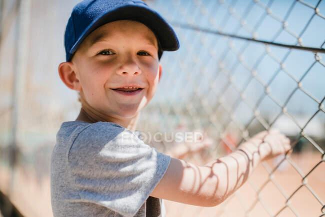 Portrait of a smiling boy standing by a baseball field, Laguna Beach, California, United States — Photo de stock
