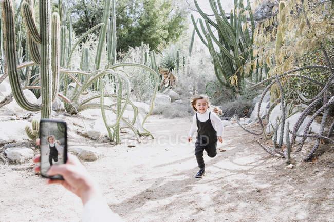 Mãe fotografando sua filha correndo no deserto, Palm Springs, Califórnia, Estados Unidos — Fotografia de Stock