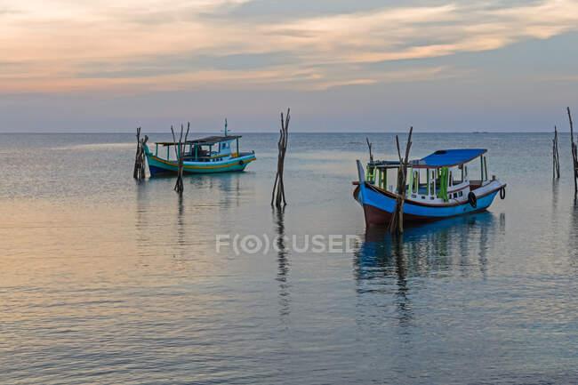 Две лодки встали на якорь в море на пляже Тани-Пандан в Индонезии — стоковое фото