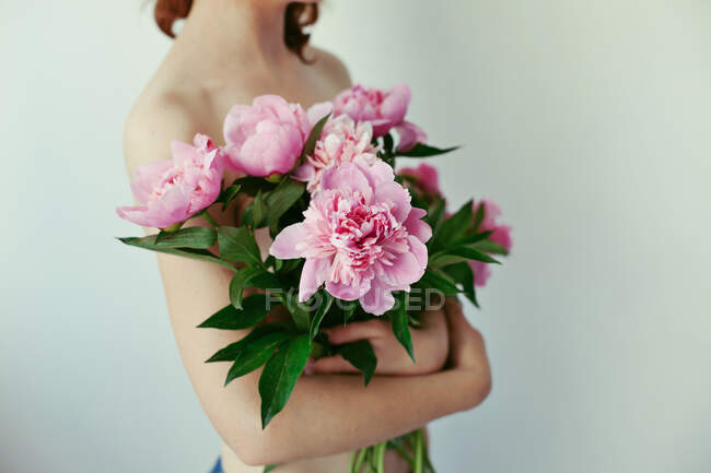 Close-up of a young woman holding a bouquet of peonies — стокове фото