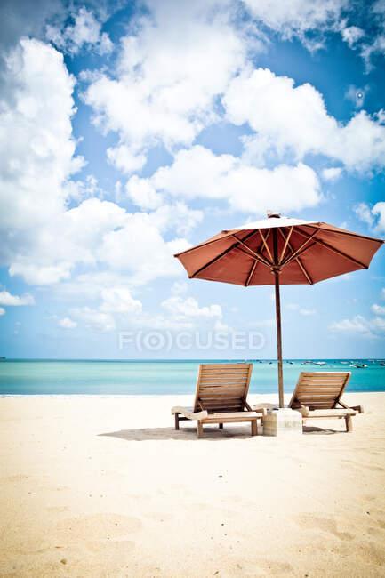 Due lettini e un ombrellone sulla spiaggia, Jimbaran Beach, Bali. Indonesia — Foto stock