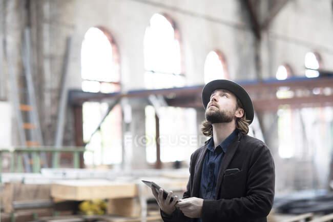 Retrato de un hombre de pie en un edificio siendo renovado mirando una tableta digital - foto de stock