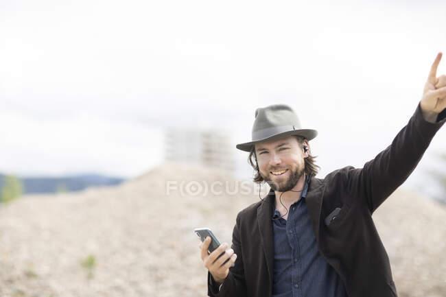 Retrato de un hombre sonriente escuchando música y haciendo una señal de cuerno - foto de stock
