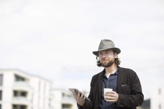 Retrato de un hombre parado al aire libre sosteniendo una taza de café y una tableta digital - foto de stock