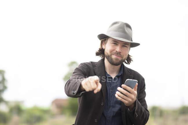 Retrato de un hombre sonriente parado al aire libre sosteniendo un teléfono móvil y señalando - foto de stock