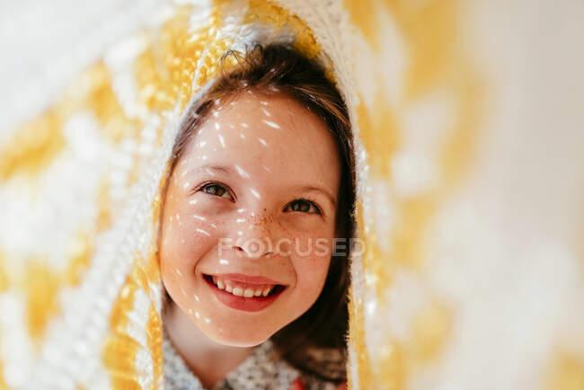 Niña riendo con pecas cubiertas de tela y rayos de sol en la cara - foto de stock