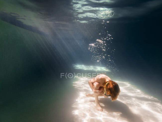 Niño acurrucado en el fondo de una piscina - foto de stock
