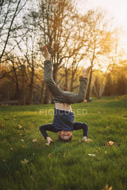 Мальчик, делающий подставку в саду, Соединенные Штаты — стоковое фото