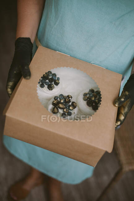 Woman holding a box of mini Pavlova desserts with blueberries and blackberries — Stock Photo