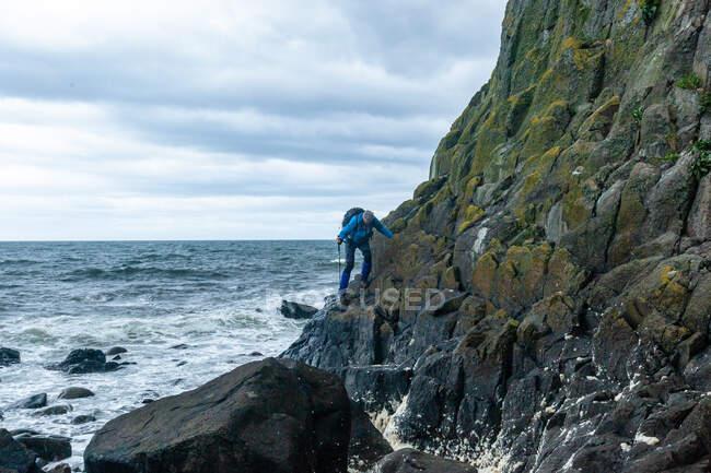 Man hiking across coastal rocks, Bennan Head, Arran Coastal Way, Isola di Arran, Scozia, Regno Unito — Foto stock